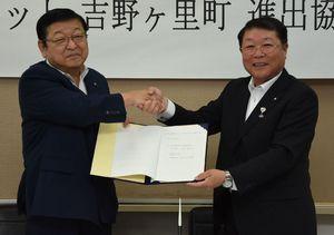 進出協定に締結し、握手を交わす秋本英樹社長(左)と伊東健吾町長=吉野ヶ里町役場