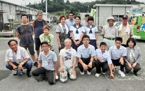 二本松市の仮設住宅を訪れ、避難者と記念撮影した松梅校中学部の生徒たち=2014年(提供)