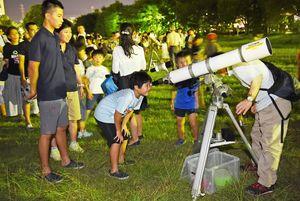 15年ぶりに大接近した火星を見ようと望遠鏡をのぞく子どもたち=佐賀市のどん3の森公園(撮影・鶴澤弘樹)