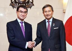 会談前に握手する河野外相(左)とシンガポールのバラクリシュナン外相=12日、シンガポール(共同)