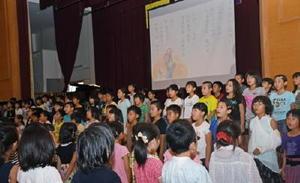 音楽物語の「一つの花」で合唱する4年生の児童たち=佐賀市立鍋島小学校の体育館