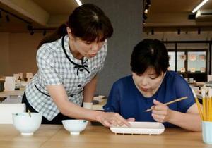 佐賀県陶磁器工業協同組合が7月1日から始める絵付け体験。同組合職員がポイントなどを説明する=有田町外尾町の同協同組合