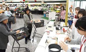学生から食材の栄養成分について説明を受ける来店客=佐賀市のアルタ新栄店