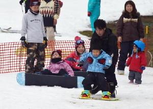 思い思いに初滑りを楽しむ人たち。5歳の男の子(手前)は初めてのスノーボードで、父親の手を借りて滑り降りていた=佐賀市富士町の天山スキー場