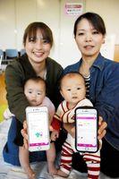 唐津市が運用を始めた母子手帳アプリ「からつっこアプリ」の画面をかざす親子=唐津市千代田町の唐津市保健センター