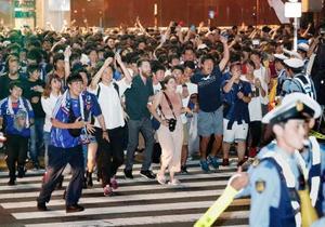 サッカーW杯の日本―セネガル戦が引き分けに終わり、東京・渋谷駅前のスクランブル交差点で盛り上がる人たち=25日未明