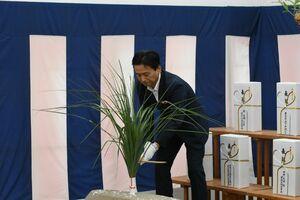 鎌でカヤを刈る所作をする「刈初の儀」を行う山口祥義知事=佐賀市のSAGAサンライズパーク