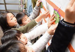 願い事を書いた絵馬を貼り付ける子どもたち=吉野ヶ里町の三田川児童館