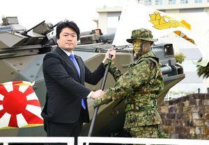 山本朋広防衛副大臣(左)から隊旗を授与される青木伸一水陸機動団長=佐世保市の相浦駐屯地