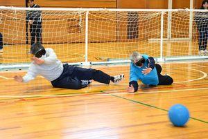 体を投げ出してボールを止める参加者=唐津市和多田の市文化体育館