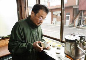 太陽光の下でお茶を入れ、出来具合を確かめる小野原栄信さん=嬉野市の小野原製茶問屋