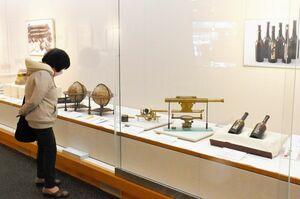 地球儀や天体観測器具、ぶどう酒の瓶などが並ぶ企画展「武雄のキセキ 蘭学への挑戦」=武雄市図書館・歴史資料館