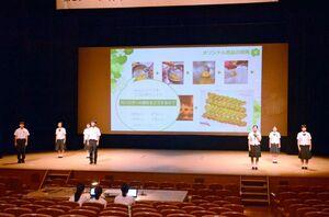地域の環境問題解決のため、竹を使った商品開発の取り組みを報告した鳥栖商高の生徒たち=佐賀市文化会館
