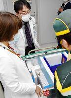 新型コロナウイルスのワクチンが搬入され、運送業者の荷ほどきに立ち会う担当者=5日午前、佐賀市の佐賀大医学部附属病院