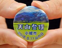 「山の日」の天山登山者に配る記念バッジ