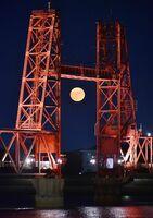 ライトアップされた筑後川昇開橋越しに見えた「中秋の名月」=21日午後7時、佐賀市諸富町から撮影