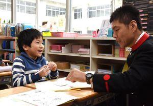 石原資展局長と話して、年賀状を書くイメージを膨らませる=佐賀市の開成小学校