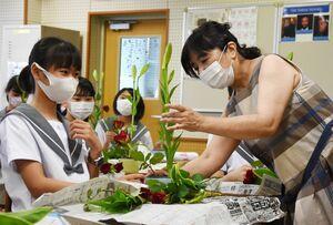 穴井貴遙さん(右)に指導を受けながら花を生ける生徒=佐賀市の佐賀大附属中学校