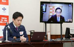 関西3府県のオンライン会議に出席した大阪府の吉村洋文知事。モニターは京都府の西脇隆俊知事=23日午後、大阪府庁