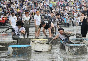 鹿島ガタリンピックで、泥まみれになりながら競技を楽しむ参加者=2019年6月、鹿島市の七浦海浜スポーツ公園