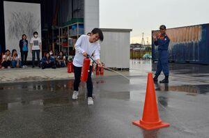 消火器で防火訓練を行うミャンマーからの留学生=佐賀市の県消防学校