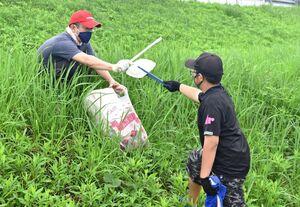 釣り場周辺のごみ拾いをするボランティアの親子=伊万里市山代町