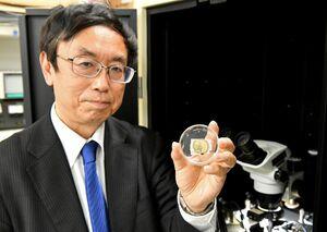 ダイヤモンド半導体を使った電子部品を持つ嘉数誠教授=佐賀市の佐賀大本庄キャンパス