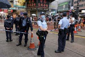 12日、香港中心部の繁華街コーズウェイベイで規制線を張って警戒する警察官(共同)
