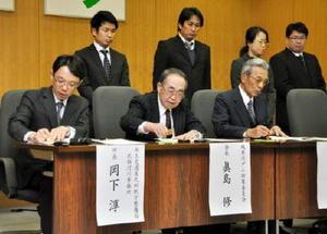 城原川ダムの詳細調査に関する協定に調印する武雄河川事務所の岡下淳所長(左)や住民団体代表=神埼市役所