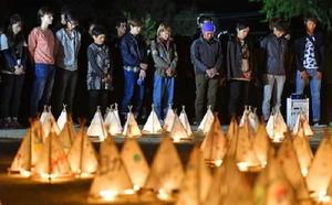 熊本地震の「本震」から半年を迎え、明かりがともされた灯籠の前で黙とうする、地震で閉鎖した南阿蘇村のキャンパスに通っていた東海大生と地元住民ら=16日午後、熊本県南阿蘇村