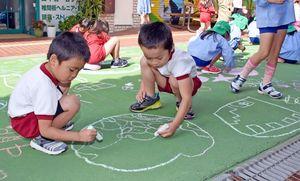 商店街の路上に思い思いの絵を描く子どもたち=基山町のモール商店街グリーンロード