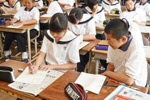 佐賀新聞を教材に自分の体験を記事にまとめる生徒たち=伊万里市黒川町の青嶺中