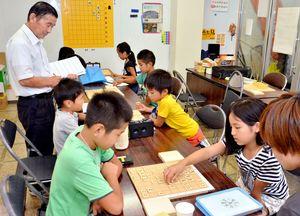 小学生向けの将棋入門教室を開いている内山博さん(左)=基山町の基山モール商店街まちなか公民館