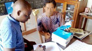葉隠研究会がまとめた教本を使い、ベナン・コトヌー市の「たけし日本語学校」で開く葉隠の特別授業について打ち合わせする教師たち(提供)