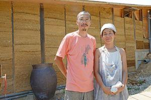 版築の壁の前で「自然の音に耳を傾けて滞在を楽しんでほしい」と話す高岡盛志郎さん、博子さん夫妻