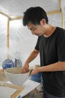 受賞作を制作中の馬場康貴さん。陶土が乾かないよう、ビニールで囲った室内に加湿器を備え、地道な作業を続けた=岐阜県多治見市の多治見市陶磁器意匠研究所(昨年8月撮影)