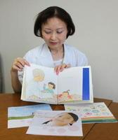 がんの親が子どもに伝える際に参考になる絵本を手にする大沢かおりさん