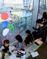 素描家の福田尚平さん(右)と一緒にガラス面のキャンパスに楽しい絵を描く子どもたち=武雄市の県立宇宙科学館