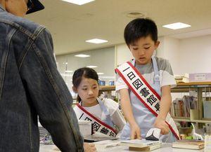 本貸し出しを体験している循誘小学校4年の西村太一君と納富千春さん=佐賀市立図書館