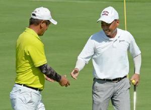 男子60歳以上の部 プレーオフ終了後、健闘をたたえ合い握手する深谷澄男(唐津市、左)と松尾秀明(伊万里市)=花祭ゴルフ倶楽部