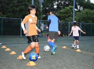 女子同士で楽しそうに練習するスクール参加者=唐津市鏡の佐賀県フットボールセンター