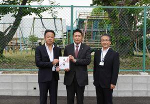 ネットフェンスを寄贈したG-stageの栗山清規会長(左)ら=みやき町の中原小南側