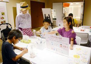 植物色素を使ってコースターを作る子どもたち=佐賀市のバルーンミュージアム
