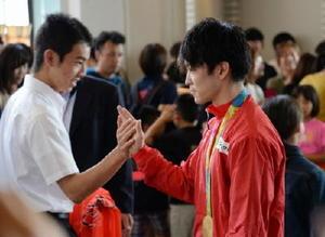 講演後、金メダルを胸に強化指定選手をタッチで送り出す内村航平さん=佐賀市文化会館大ホール