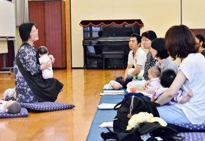 赤ちゃんの人形を使い抱っこの仕方を教える佐賀大学の佐藤珠美教授(左)=佐賀市の鍋島公民館