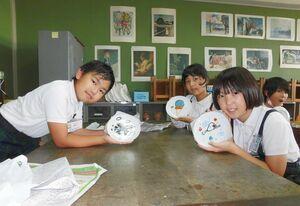 好きな絵柄を描いた皿を見せる子どもたち