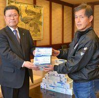 贈呈式で岩島正昭町長(左)にマスクを渡す永渕政信さん=太良町役場