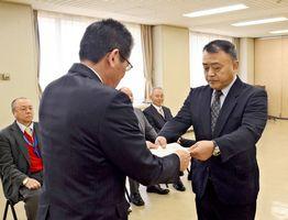 委嘱状を受け取る山口龍徳さん(右)=佐賀市の県警本部