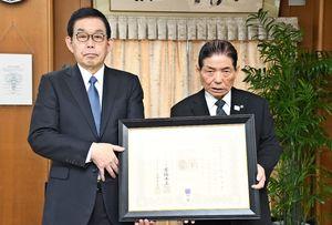 宮﨑学長(左)から紺綬褒章を受け取った古賀さん(右)=佐賀市の佐賀大学
