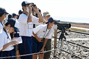 双眼鏡で野鳥を観察したり、ハンドブックで種類を調べる東与賀中の生徒たち=佐賀市の東よか干潟